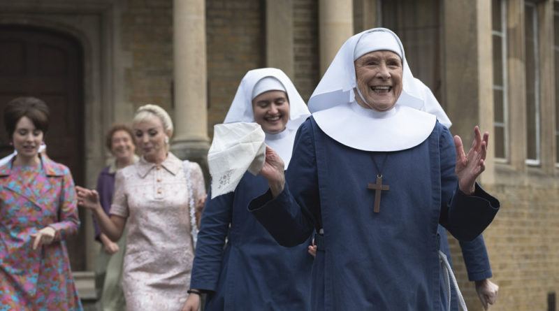 Two nuns and two young women walking out of a building